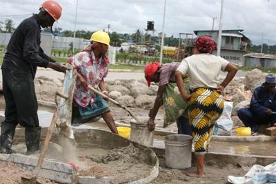 Wanawake wakishirikiana katika kazi ya kuchanganya na kubeba zege katika mradi wa EPZ unaondelea kujengwa Ubungo External, Dar es Salaam.